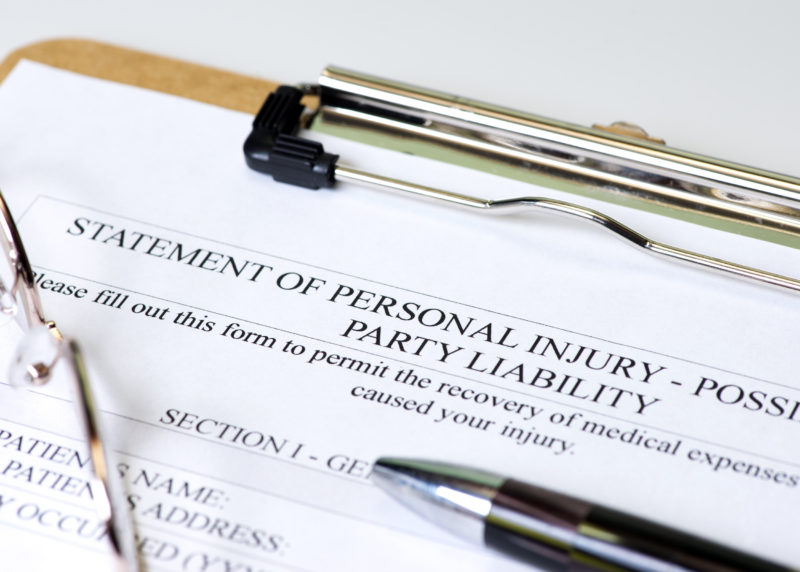 Personal injury claim on clipboard with pen and glasses.