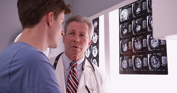 Young male adult caucasian reviewing brain xrays with mid aged physician.
