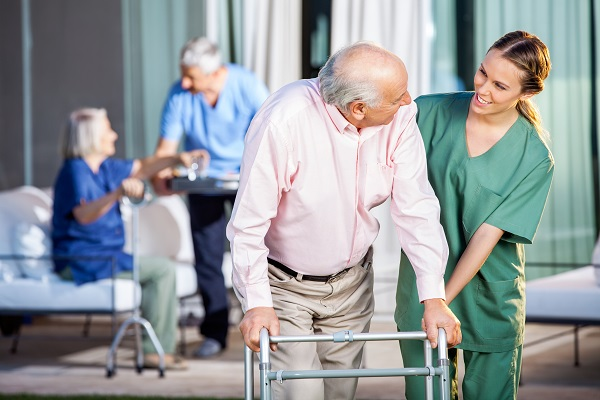 Female caretaker assisting senior man